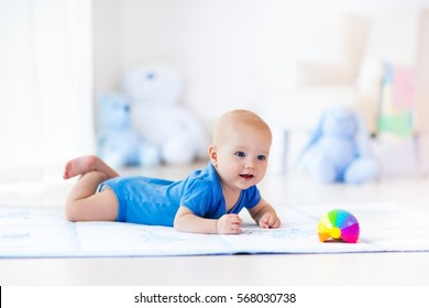 Adorable baby boy learning to crawl and playing with colorful rainbow ball toy in white sunny bedroom. Cute laughing child crawling on a play mat. Nursery, clothing and toys for little kids.