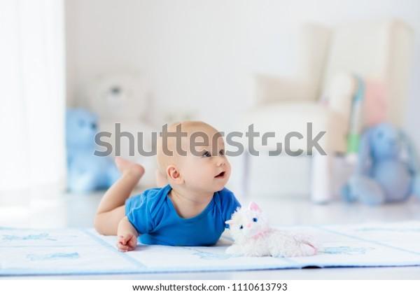 Adorable bébé garçon apprenant à ramper et à jouer avec un jouet coloré dans une chambre blanche ensoleillée. Joli enfant riant rampant sur un tapis de jeu. Intérieur de la crèche, vêtements et jouets pour petits enfants.