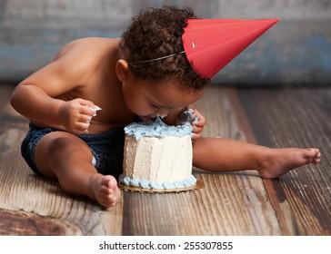 Adorable baby boy licking his birthday cake.