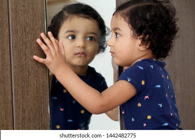 Adorable baby boy looking ta his reflection in mirror