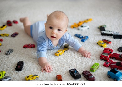 Adorable baby boy, lying on the floor, toy cars around him , looking at the camera, shot from above