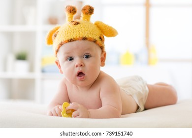 Adorable baby boy lying on tummy and weared funny hat