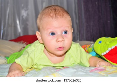 Adorable baby boy on bed. Newborn child relaxing in bed. Happy child.