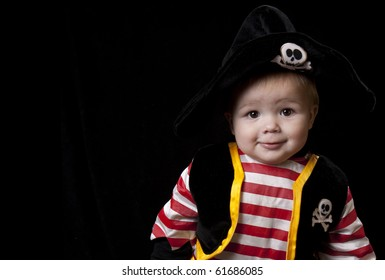 Adorable baby boy in a pirate costume for Halloween on a black background.