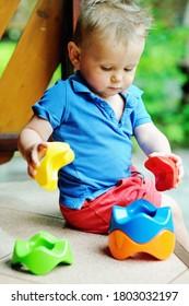 Adorable bébé garçon jouant avec une sorcière colorée en plein air pendant les chaudes journées d'été