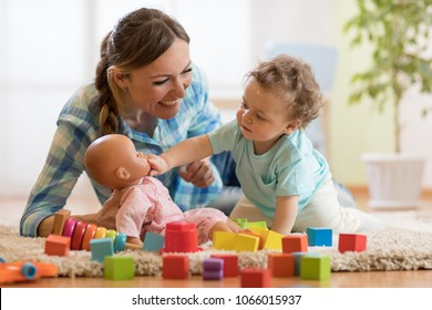 Adorable baby boy playing with doll in nursery room. Happy healthy child having fun with colorful different toys at home.