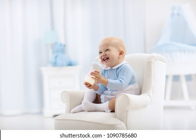 Adorable baby boy playing on a blue floor mat and drinking milk from a bottle in a white sunny nursery with rocking chair and bassinet. Bedroom interior with infant crib. Formula drink for infant.