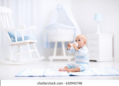 Adorable baby boy playing on a blue floor mat and drinking milk from a bottle in a white sunny nursery with rocking chair and bassinet. Bedroom interior with infant crib. Formula drink for infant