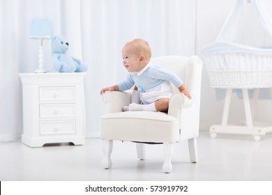 Adorable baby boy playing in white sunny bedroom. Happy child relaxing in toy chair on play mat. Nursery and play room for young children. Infant furniture, clothing, textile and bedding for kids