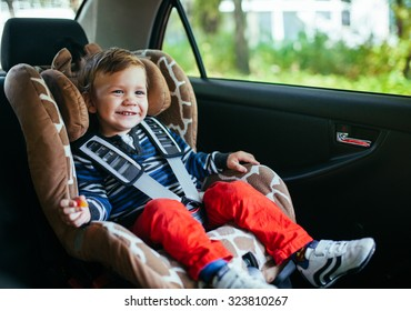 Adorable baby boy in safety car seat.