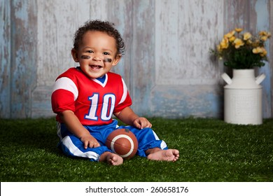 Adorable baby boy sitting in the grass, wearing a football uniform.
