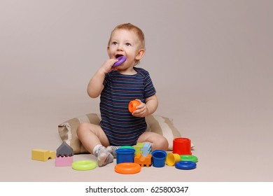Adorable baby boy sitting and playing toys.