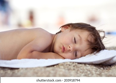 Adorable baby boy, sleeping on the beach, exhausted after fun day at the beach