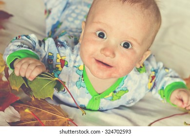 Adorable baby boy smiling and looking up. Funny autumn portrait with maple leaves. Image with vintage filter
