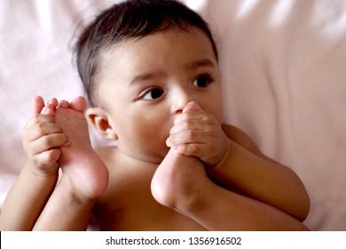 Adorable baby boy sucking his toe