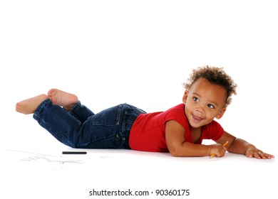 An adorable baby boy using a pencil and crayon to draw on the floor around him.  On a white background.