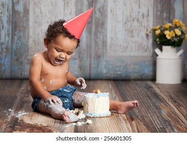 Adorable baby boy wearing a red party hat and eating a small birthday cake.