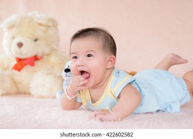 Adorable baby boy in white sunny bedroom. Newborn child relaxing in bed.