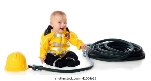 And adorable baby boy winking while wearing a fireman's suit, wit his hat and hose nearby.  Isolated on white.