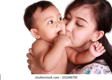 Adorable baby chewing her finger and kissed by her mom, isolated on white background