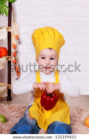 e07c4773d adorable baby cooking in kitchen. little cute child in costume of Cook. the  happy