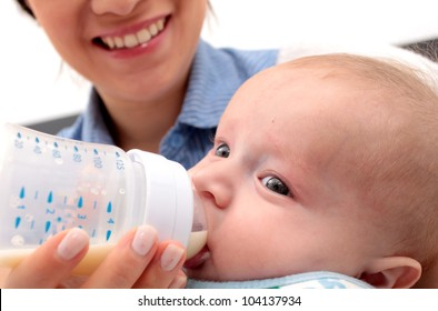 Adorable baby drinking a bottle - focus in the face