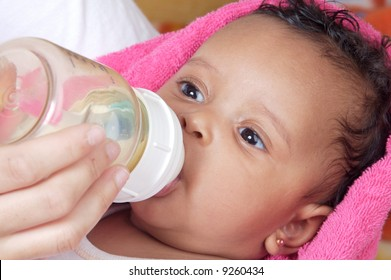 Adorable baby drinking a bottle - focus in the face -