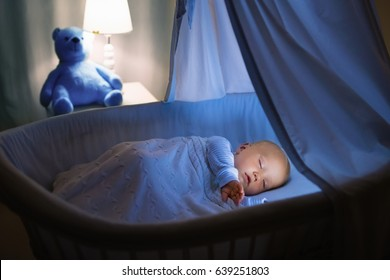 Adorable baby drinking milk in blue bassinet with canopy at night. Little boy in pajamas with formula bottle getting ready to sleep in dark room with crib, lamp and toy bear. Bed time drink for kids.