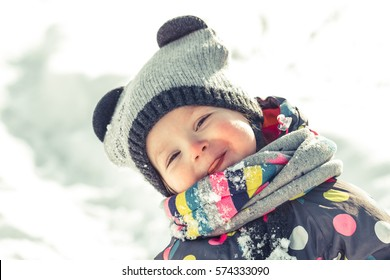 Adorable baby eat cold snow from mittens in sunny winter park