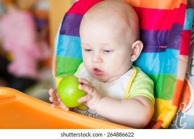 Adorable baby eating apple in high chair. Baby's first solid food
