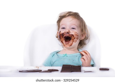 Adorable baby eating chocolate bar for the first time