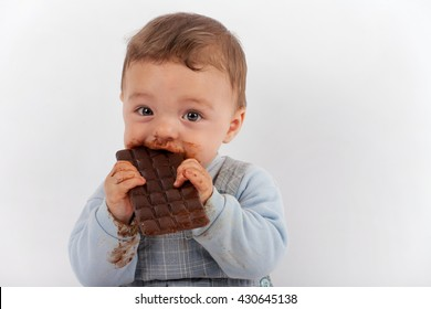 Adorable baby eating a plate of chocolate