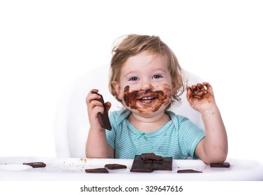 Adorable baby with face covered in chocolate