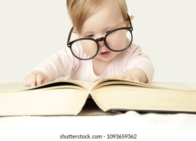 Adorable baby in front of big thick book, studio shot