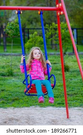 Adorable baby girl with beautiful curly hair wearing a red dress enjoying a swing ride on a playground in a park on a nice sunny autumn day