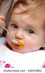 Adorable baby girl being fed by mom with a spoon in the park
