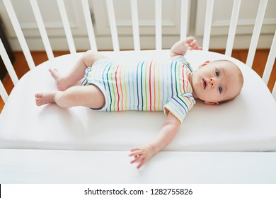 Adorable baby girl in co-sleeper crib attached to parents' bed. Little child having a day nap in cot. Infant kid in sunny nursery