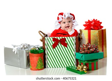 An adorable baby girl dressed as Mrs. Santa in a big Christmas-decorated box and surrounded by others.