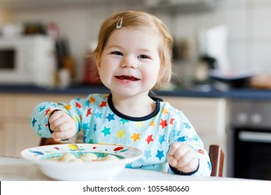 Adorable baby girl eating from spoon vegetable noodle soup. food, child, feeding and people concept