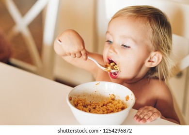 Adorable baby girl with good appetite eats pasta with tomato sauce