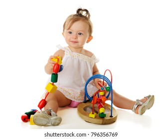 An adorable baby girl happily playing with big, wooden beads -- some on a string, others on a wire frame.  On a white background.
