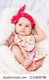 Adorable baby girl with headscarf lying in the basket