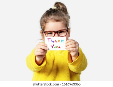 Adorable baby girl is holding a paper with a Thank you note. Silent communication concept.