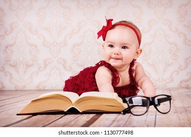 Adorable baby girl lying on the floor and reading a book with glasses and ribbon