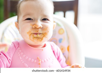 An Adorable baby girl making a mess while feeding herself