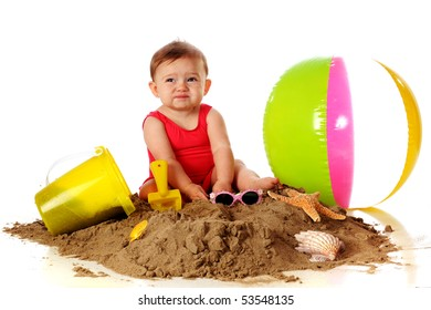 """An adorable baby girl making a """"Yuck"""" face while playing in the sand with beach toys."""