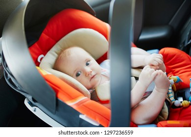 Adorable baby girl in modern car seat. Little kid traveling by car. Child safety on the road. Trip with an infant.