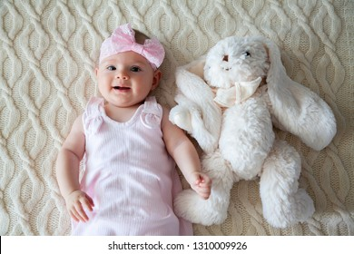 adorable baby girl in pink dress lying near white rabbit toy