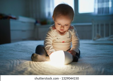 Adorable baby girl playing with bedside lamp in nursery. Happy kid sitting on bed with nightlight. Little child at home in the evening before sleep