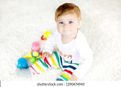 Adorable baby girl playing with educational toys in nursery. Happy healthy child having fun with colorful different toys at home. Baby development and first steps, learning to play and to grab.